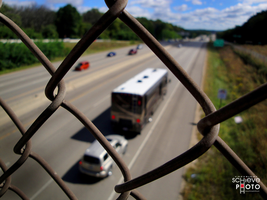Beltline traffic in Madison, Wisconsin through chain link fence.