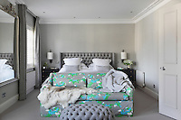 The bright blue and green birds on the sofa stand out against the grey, monochone tones of this Turner Pocock bedroom