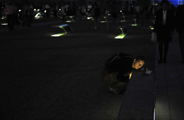 Miriam van Gool of the Netherlands reads a name on a marker during the opening of the Pentagon Memorial honoring those who passed away at the site on 9/11/2001, September 11, 2008.