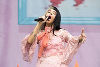 "Singer Melanie Martinez, known for being a contestant on the TV show ""The Voice"" performs in the rain at Music Midtown Sunday in Atlanta."