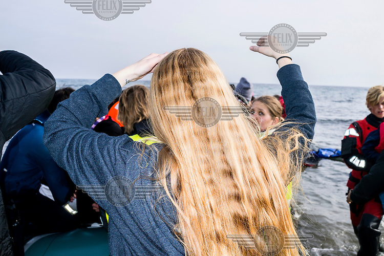 A european volunteer moves towards a boat of refugees as it reaches the shore.