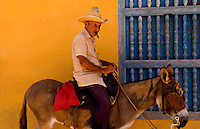 Old man riding donkey for tourists in the old colonial city of Trinidad in Cuba
