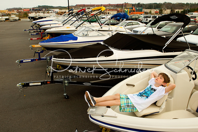 """Photography of Concord Mills Mall, a 1.4 million-square-foot mall located in Concord, NC, about 12 miles from Charlotte, NC. In this image, Robert Mullis, 9, from Fort Lawn, South Carolina, kicks back and relaxes in one of the many boats on display in the parking lot of Bass Pro Shops Outdoor World at Concord Mills.  Mullis said """" One day I will one of these of my own."""" Photo is part of a photographic series of images featuring Concord, NC, by photographer Patrick Schneider."""