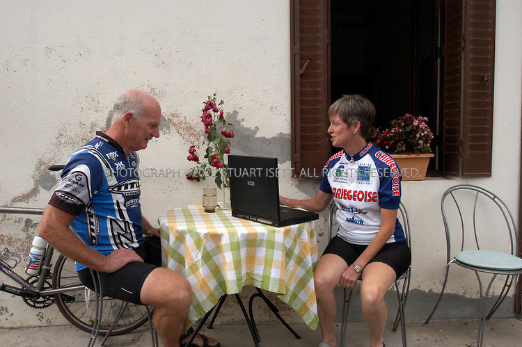 8/26/2003--Mauléon Barousse, France..Linda (49?wife) and Sandy (61, husband) Beebe, both originally from Winthrop, Washington USA,  outside their small home in Southern France. Their new Dell computer that was attacked by the 'Blaster virus' on August 23rd. Unable to log back on to the internet the couple eventually used an old Dell laptop (shown in photo) with Windows 98 on it to download anti-virus softtware...Mauléon Barousse,is a sleepy village in the Hautes Pyrenees province of France near the Spanish border. Both of the Beebes are cycling enthusiasts and spend their summers cycling in the hills around their home. Sandy Beebe is a retired United Airlines pilot....All photographs ©2003 Stuart Isett.All rights reserved.This image may not be reproduced without expressed written permission from Stuart Isett.