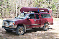 A Toyota T100 truck with a canoe on top.
