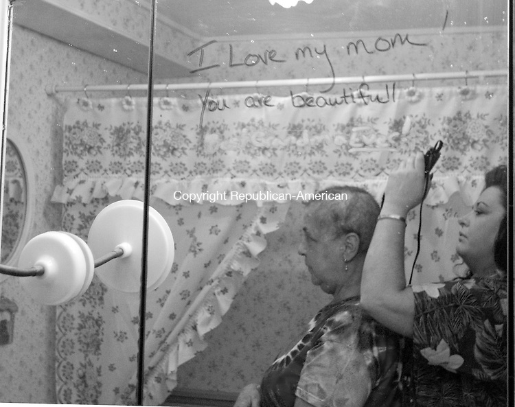 MIDDLEBURY, CT - 24 DECEMBER 2007 -112008JT17-<br /> Marie Tyrrell has her head shaved by daughter Tracie Marcil at Marie's house in Middlebury on Christmas Eve 2007, as seen through a bathroom mirror on which Tracie wrote, &quot;I love my mom! You are beautiful!&quot; Having gone through her fourth round of chemotherapy, this was Marie's second time having her head shaved since being diagnosed with stage four lung cancer. The hair cut followed a tropical-themed Christmas party at the empty house that was put up for sale after Marie was diagnosed.<br /> Josalee Thrift / Republican-American