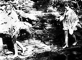 Girls walk along the banks of the creek.