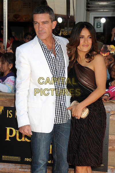 Antonio Banderas and Salma Hayek.The L.A. Premiere of 'Puss in Boots' held at The Regency Village Theatre in Westwood, California, USA..October 23rd, 2011.half length dress black brown sheer one shoulder gold clutch bag jeans denim white suit jacket check shirt .CAP/ADM/BP.©Byron Purvis/AdMedia/Capital Pictures.