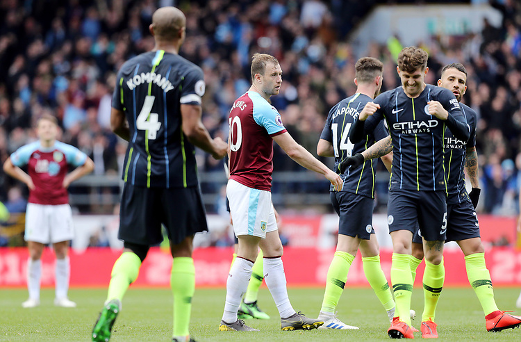Burnley's Ashley Barnes looks dejected as Manchester City's John Stones and Vincent Kompany celebrate victory at the final whistle<br /> <br /> Photographer Rich Linley/CameraSport<br /> <br /> The Premier League - Burnley v Manchester City - Sunday 28th April 2019 - Turf Moor - Burnley<br /> <br /> World Copyright © 2019 CameraSport. All rights reserved. 43 Linden Ave. Countesthorpe. Leicester. England. LE8 5PG - Tel: +44 (0) 116 277 4147 - admin@camerasport.com - www.camerasport.com