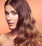 Beauty portrait of a young woman with beautiful long wavy brown hair