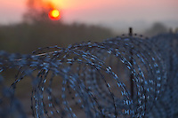 Sun rises behind the razor wire border fence between Hungary and Serbia near Roszke (about 174 km South of capital city Budapest), Hungary on August 30, 2015. ATTILA VOLGYI