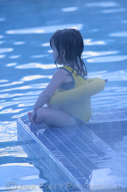 Young girl sitting on the edge of a pool and hot tub with steam rising around her.
