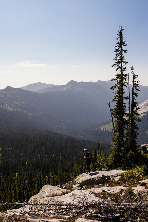 A man in his mid-thirties checks a GPS unit while standing on a large rock in the Selkirk range of Northern Idaho.