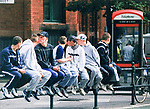 © Joel Goodman - 07973 332324 . 24/08/2003 . Manchester , UK . A row of seven youths wearing tracksuits, baseball caps and trainers , sit on railings at the side of a street in Manchester . Photo credit : Joel Goodman