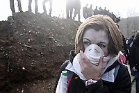 Skouries, Greece Sunday 23 November 2014<br /> Pictured: A female protester struggles to breathe<br /> Re: Riot police called to break up a protest by local residents against a Canadian-run goldmine in Skouries, in the Chalkidiki area. Eldorado firm has been accused of dumping toxic waste generated during gold processing in northern Greece, into local rivers. Teargas was used by the police to disperse the protesters who retaliated with pyrotechnics.