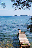 A man sitting on a wooden jetty on the stony beach looking towards the sea half hidden by pine trees. Orebic town, holiday resort on the south coast of the Peljesac peninsula. Orebic town. Peljesac peninsula. Dalmatian Coast, Croatia, Europe.