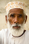 An old Omani bearded man dressed in white with a traditional hat at the Muttrah Souq in Muscat, Oman.