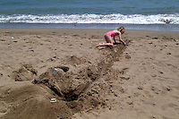 Young girl on the beach digging trench to the water in Barcelona, Spain.