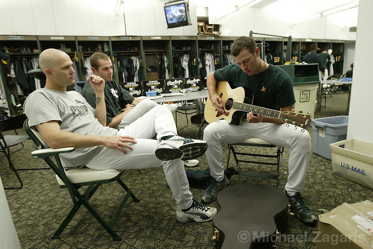 OAKLAND, CA - MAY 22:  Tim Hudson, Bobby Crosby and Rich Harden of the Oakland Athletics practice guitar before the MLB game against the Kansas City Royals at Network Associates Coliseum on May 22, 2004 in Oakland, California. The A's defeated the Royals 5-4. (Photo by Michael Zagaris/MLB Photos via Getty Images)