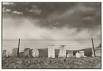 Scan of vintage print. Rural graveyard with wire fence.