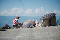 roadside fans waiting for riders to pass by and try to escape the heat on the very last climb of the 100th Tour de France<br />