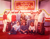D.B.'s Delight crew and cast pose on the set, sitting in front row, left to right, Stage Manager Jerry Rock, D.B. Doorbell aka Bobby Miller and Associate Producer Linda Haverstick (Foster). Back row, Show Intern, Show Camera Operator, Director Carl Petre, Host Bobby Day, Producer Debi Pittman (Wilkey), Senior Producer & Show Creator Jan Landis, Technical Director Ken Wilkey, Audio Director Don Lucy and Camera Operator Tony Hornsberger, 1983 --????