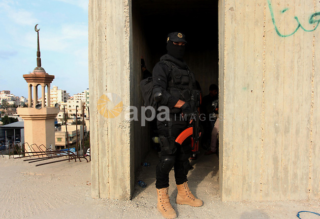 A Palestinian Islamic Jihad militant stands guard on a roof during a rally marking the 29th anniversary of the movement foundation in Gaza City October 21, 2016. Photo by Ashraf Amra
