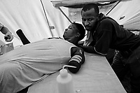 Port Au Prince, Haiti, Jan 23 2010.Islaine Celmé, 38, who lost her right and and left arm in the disaster is comforted by her husband Carlo Celmé, 41; thye both displya very poitive spirit in front of their personal tragedy.The Belgian B-Fast team has set up a field hospital in Delmas 33; 2 surgeons treat vicitms of hevy traumatisms..