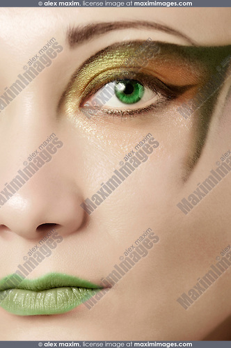 Stock photo of a Beautiful female face with a creative make-up in green colors Fashion makeup beauty treatment Vertical
