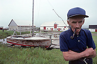 Ile D'Orleans, Quebec City Area, Canada, June 8, 1984. An old inhabitant of the island  in front of his sail boat.