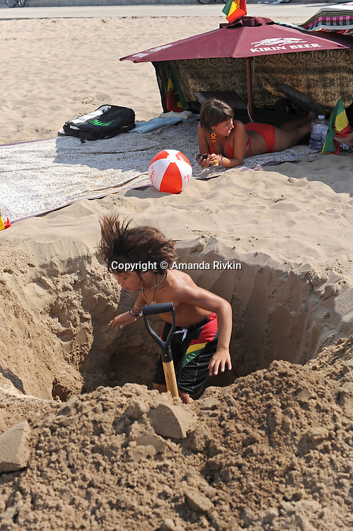 A young boy digs a hole in the sand as a woman rests nearby under a beach umbrella at North Avenue beach in Chicago, Illinois on August 18, 2008.