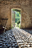 Inside a garden building with rough stone walls and a cobbled floor. An open wrought-iron gate leads to a garden beyond.