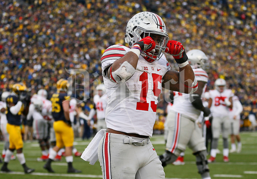 Ohio State Buckeyes running back Ezekiel Elliott (15) pretends to cry while celebrating scoring a touchdown during the fourth quarter of the NCAA football game at Michigan Stadium in Ann Arbor on Nov. 28, 2015. Ohio State won 42-13. (Adam Cairns / The Columbus Dispatch)