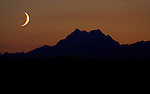 A waxing moon sets over the Olympic Mountains  on Friday, July 24, 2009. In  the northern hemisphere, if the left side of the Moon is dark then the light part is growing, and the Moon is referred to as waxing (moving towards a full moon). If the right side of the Moon is dark then the light part is shrinking, and the Moon is referred to as waning (moving towards a new moon).  ©2012.  Jim Bryant All RIghts Reserved..