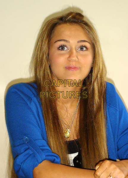 "MILEY CYRUS.Press conference for ""Hannah Montana: The Movie"" at the Four Seasons Hotel, Beverly Hills, California, USA..March 28th, 2009.half length blue tan tanned top.CAP/AW.©Anita Weber/Capital Pictures."