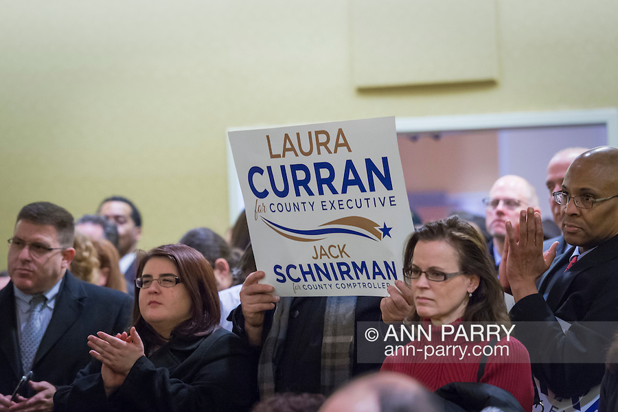 Uniondale, New York, USA. January 30, 2017. Audience members clap and hold up signs supporting Laura Curran, candidate for Nassau County Executive, and Jack Schnirman, candidate for County Comptroller. The candidates each received an endorsement from Democratic Party leaders. Curran is in her 2nd term as Nassau County Legislator for the 5th District. A primary is expected for County Exec. Jack Schnirman is Long Beach manager and has never held elected office.