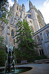 The turrets of the Washington National Cathedral in Washington, DC rise up toward the sky.  Outside, a fountain spurts water in the courtyard.
