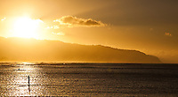A standup paddler with a kayaker in the distance at sunset at Kaena Point, Oahu