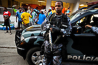 A Brazilian policeman guards the street during the Carnival parade in the favela of Rocinha, Rio de Janeiro, Brazil, 20 February 2012. Rocinha, the largest shanty town in Brazil and one of the most developed in Latin America, has its own samba school called GRES Academicos da Rocinha. The Rocinha samba school is very loyal to its neighborhood. Throughout the year, the entire community actively participate in rehearsals, culture events and parades related to the carnival.