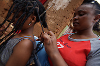 Asmar Maharate, 18, sex worker from Goldon, has hair extensions added to her by a colleague in Babile,  Ethiopia on Monday August 14 2006..tens of young girls work in small bars in the boarder town of Babile, where the rat of HIV infections is among the highest in the country. they seel their bodies for less than 2 USD. None of these girls test for HIV and frequently are frequently forced into unprotected sex..Ethiopia is one of the countries most affected by HIV/AIDS. Of its population of 77 million, three million are HIV-positive, according to government statistics. Every day sees 1,000 new infections. A million children under 14 have lost one or both parents to AIDS, and 200,000 children are living with AIDS. That makes Ethiopia the country with the most HIV-positive children.