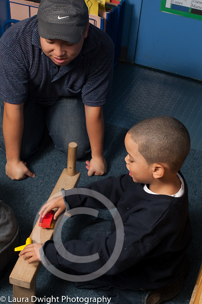 Preschool 3-4 year olds male teacher in training playing with boy  in block area horizontal