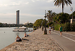 People enjoying waterside on the banks of the Guadalquivir river, Seville, Spain