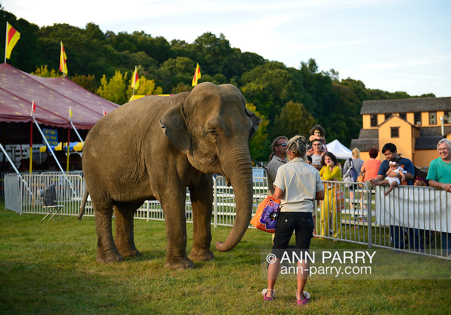 Old Bethpage, New York, USA. 28th September 2014. Families look and learn about Minnie the 8,000 pound African elephant at the Elephant Show, with the Exhibition Hall in the background, at the 172nd Long Island Fair, a six-day fall county fair held late September and early October. A yearly event since 1842, the old-time festival is now held at a reconstructed fairground at Old Bethpage Village Restoration.
