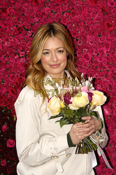CAT DEELEY.Photocall with a Map of Africa, made from 10,000 African Roses, to mark the launch of FLOWE (RED), the new online flower service that will generate funds to help Africa, Covent Garden, London, England..February 2nd, 2010.half length jacket flowers beige bouquet .CAP/CJ.©Chris Joseph/Capital Pictures.