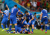 Sokratis Papastathopoulos of Greece is mobbed by team mates as he celebrates scoring his goal to make the score 1-1
