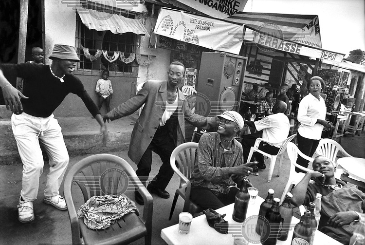 © Dieter Telemans / Panos Pictures..Music in Kinshasa, Democratic Republic of Congo. 06/2001..Terrasse in the neighbourhood Matete..Born with music in their blood, the Congolese can't help dancing. These elegantly dressed young men call themselves les Sappeurs. La Sape (Soci?te des ambianceurs et personnes ?l?gantes - the cool and elegant) is about the adulation of appearance.