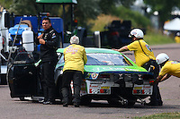 Jul. 19, 2014; Morrison, CO, USA; Safety safari members push NHRA pro stock driver Dave Connolly onto the return road during qualifying for the Mile High Nationals at Bandimere Speedway. Mandatory Credit: Mark J. Rebilas-