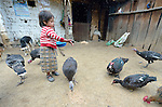 Three-year old Nyda Diaz Vasquez feeds poultry at her home in Tuixcajchis, a small Mam-speaking Maya village in Comitancillo, Guatemala.