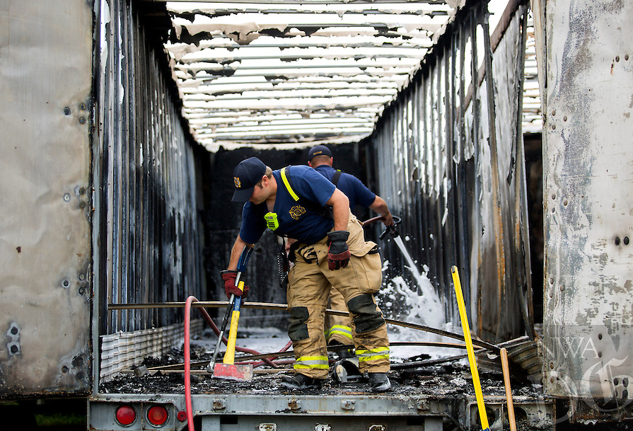 NWA Democrat-Gazette/JASON IVESTER<br /> Rogers Firefighters Derek Reaves (near) and Troy Chandler extinguish remaining hotspots inside a Hogbox trailer on Friday, June 17, 2016, following a fatal accident on Arkansas Street near E. Walker Road in Rogers. Acccording to Rogers Police, initial investigation indicates the vehicle was southbound on Arkansas Street travelling at a high rate of speed when it left the east side of the road colliding with several fence posts. The vehicle came to rest after it collided with a trailer and caught on fire with the driver still inside the vehicle. The driver of the vehicle has not been identified at this time. The body has been sent to the State Crime Lab in Little Rock for identification. The investigation is on-going.