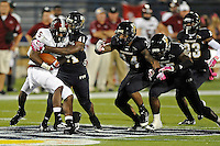 25 October 2011:  FIU linebacker Kenneth Dillard (41), with linebacker Winston Fraser (34), linebacker Jordan Hunt (25) and defensive back Terrance Taylor (23) following close behind, tackles Troy wide receiver Corey Johnson (5) in the third quarter as the FIU Golden Panthers defeated the Troy University Trojans, 23-20 in overtime, at FIU Stadium in Miami, Florida.
